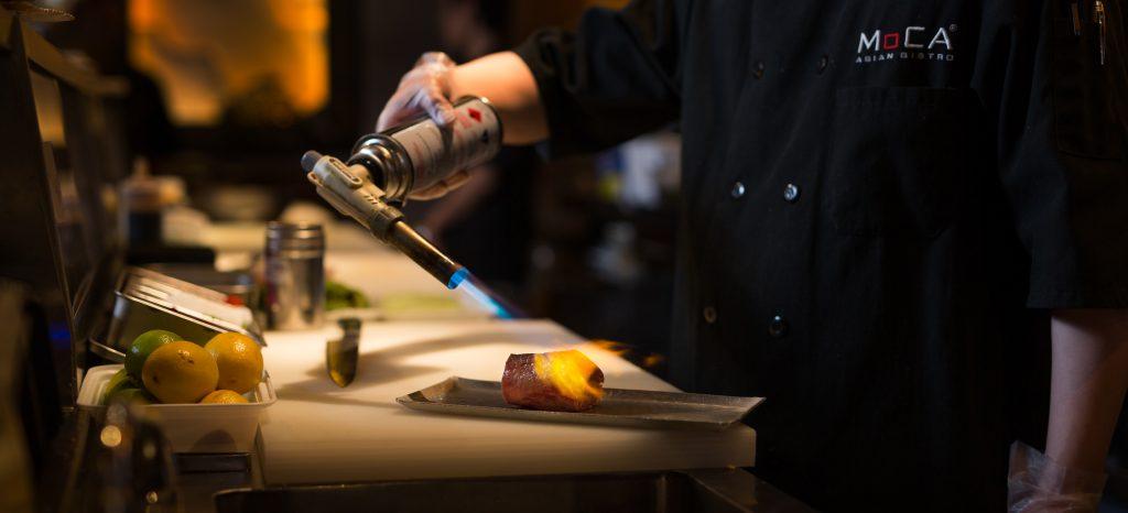 Sushi chef searing tuna sashimi
