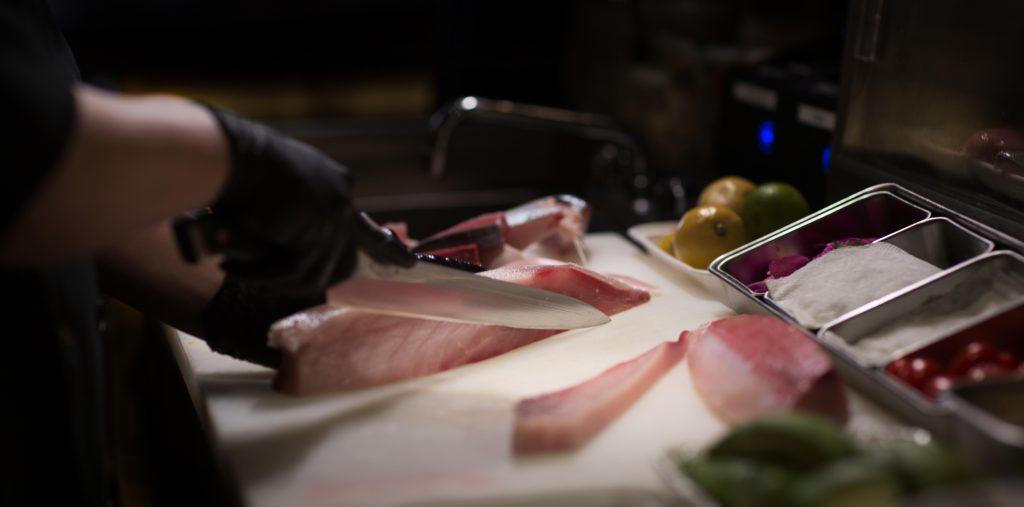 Sushi chef fileting sashimi